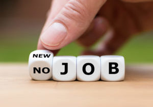 """Hand is turning a dice and changes the expression """"no job"""" to """"new job"""""""
