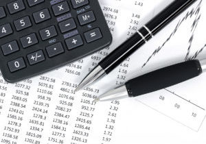 Black and white picture of financial data and graph printouts with scientific calculator and pens.