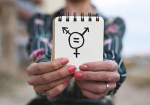 closeup of a young caucasian woman outdoors showing a notepad in front of her with a transgender symbol drawn in it